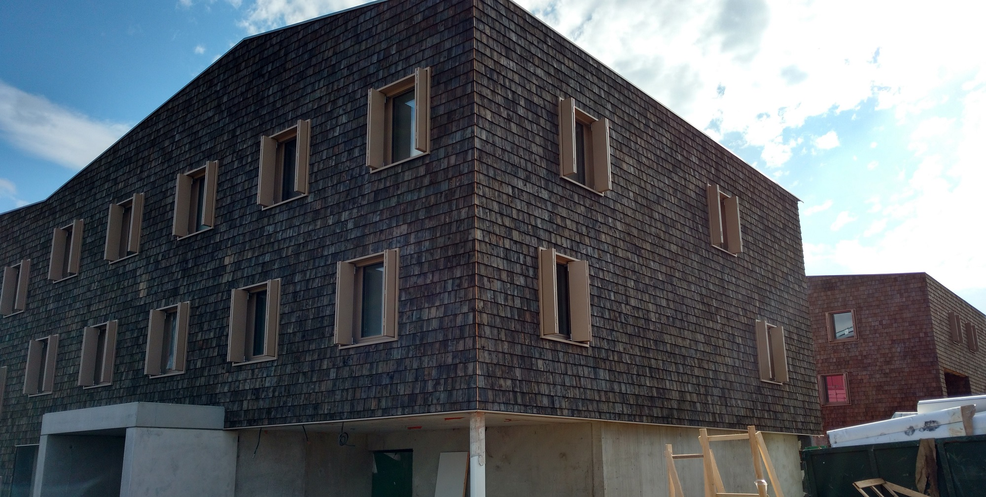 Facade and roofing in pre-greyed Soveco® Wooden Tiles